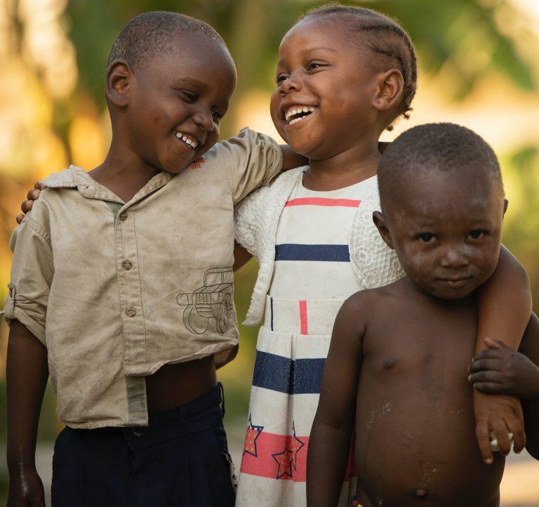 Three African children smiling, philanthropy